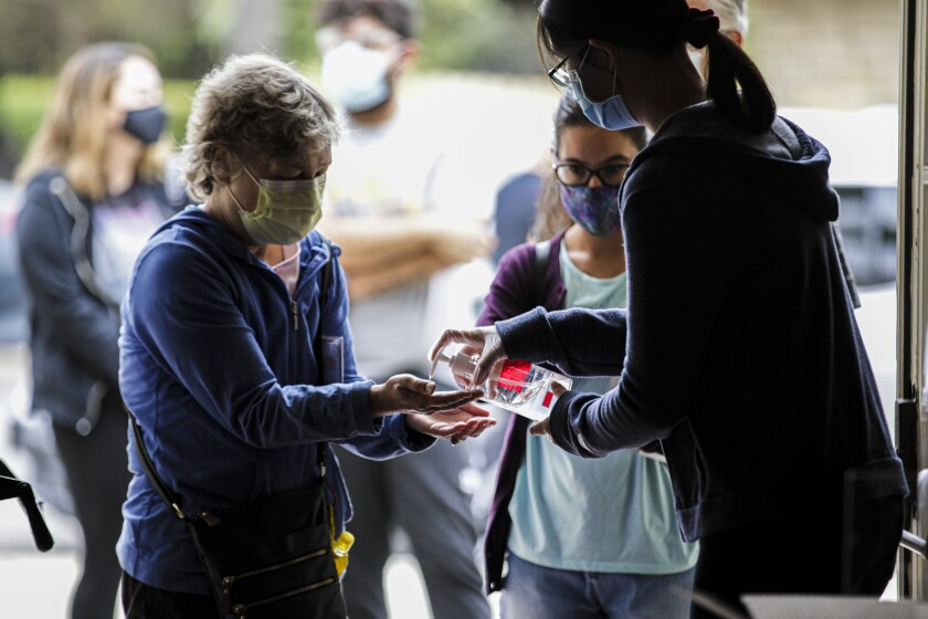 A woman in a face mask accepts hand sanitizer