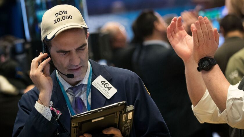 """A trader wearing a """"Dow 20,000"""" hat works on the floor of the New York Stock Exchange in December."""