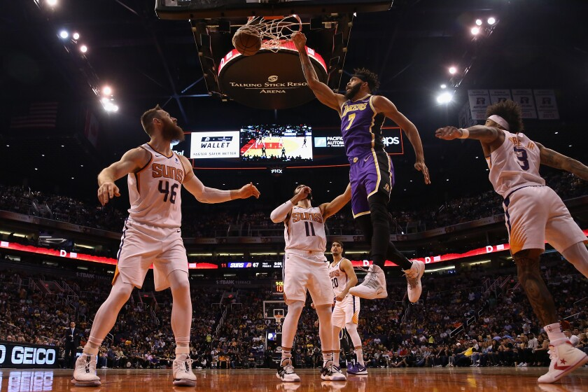 Lakers' JaVale McGee (7) slam dunks the ball over Phoenix Suns' Aron Baynes (46) during the second half on Tuesday in Phoenix.