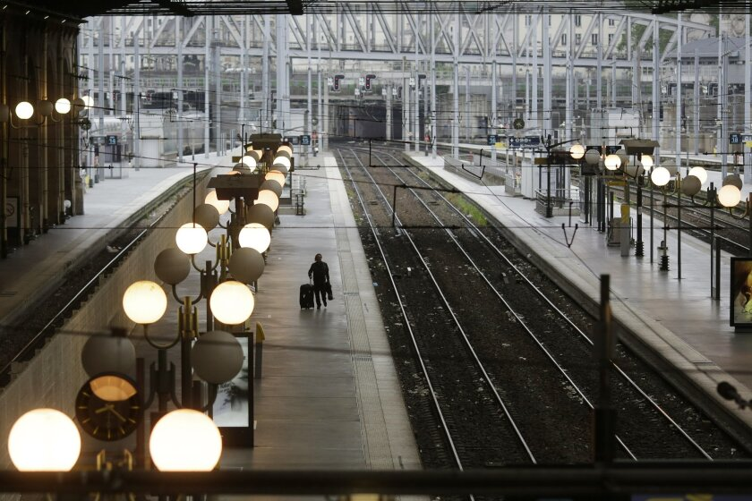 A man walks over a platforms during a railway strike at the Gare du Nord train station, in Paris, Thursday, June 2, 2016. Workers at the SNCF national rail authority, whose train service will be crucial to football'sEuro 2016 spectators, are on an open-ended strike to protest their working conditio