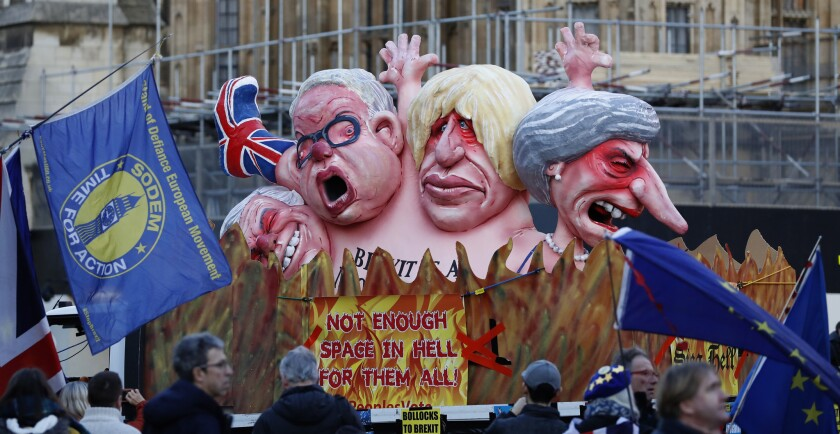 Manifestantes en contra del Brexit frente a un vehículo decorado con retratos de los principales políticos británicos, de derecha a izquierda la premier Theresa May, Boris Johnson, Michael Gove, David Davis, fuera del Palacio de Westminster el jueves 14 de febrero de 2019 en Londres. (AP Foto/Alastair Grant