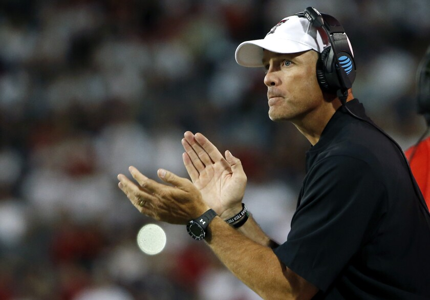 """FILE - In this Sept. 14, 2019, file photo, Texas Tech coach Matt Wells applauds his team during the first half of an NCAA college football game against Arizona in Tucson, Ariz. Wells said at the start of this fall's camp that there was no question Alex Bowman was in line to take the first snap, and it was the sophomore quarterback's job """"to solidify that role and extend his lead. It's up to him to play well."""" (AP Photo/Ralph Freso, File)"""