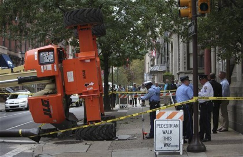 Police and fire department officials gather at the accident scene in center city Philadelphia on Monday Oct. 12, 2009, where a man operating a construction lift to work on a church roof drove over a sidewalk grate, slowly toppling the crane-like machine and sending him 125 feet to the ground. (AP Photo/ Joseph Kaczmarek)