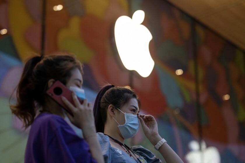 Women stand near new Apple store in Beijing
