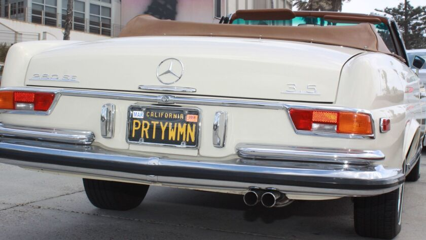 The license plate 'PRTY WMN' is in honor of Roy Orbison's 1965 hit song 'Oh, Pretty Woman.'