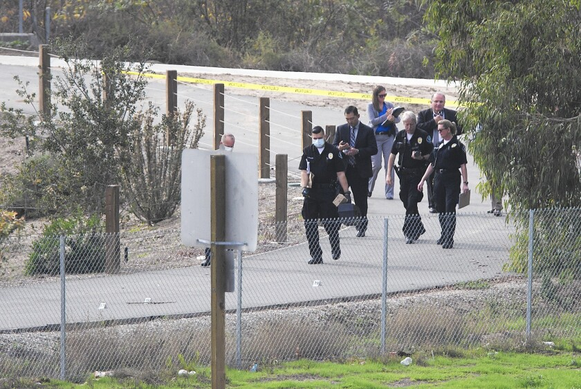 Investigators walk a bike path near the 405 Freeway in Irvine where a body was found Jan. 19. A suspect has been identified in the case.