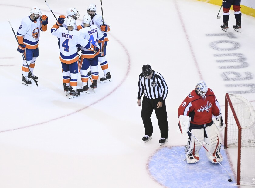 Washington Capitals goaltender Braden Holtby (70) scoops the puck from the net as the New York Islanders celebrate their goal during third-period NHL Eastern Conference Stanley Cup playoff hockey action in Toronto, Friday, Aug. 14, 2020. (Nathan Denette/The Canadian Press via AP)