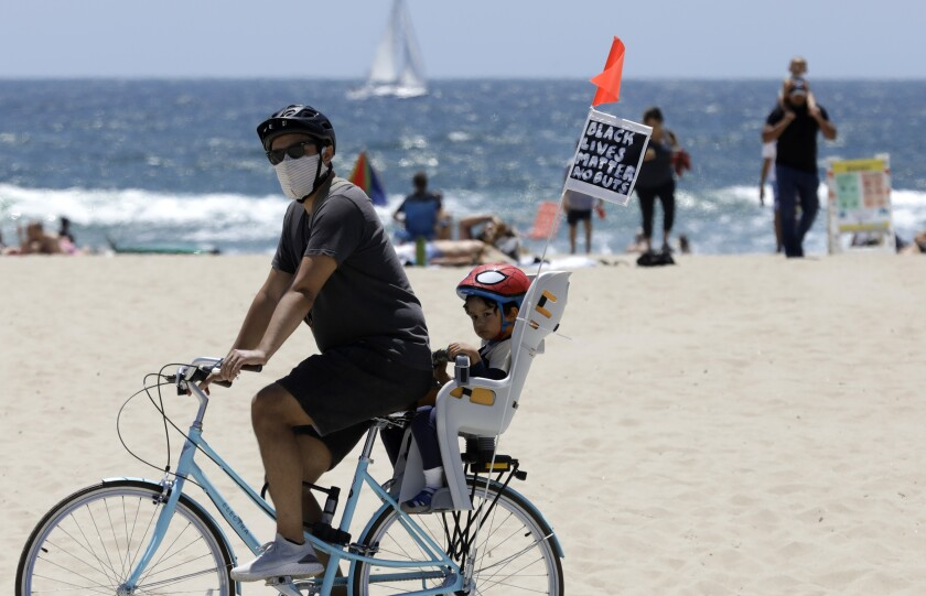 A cyclist and his passenger fly a Black Lives Matter banner in Venice Beach on Sunday.