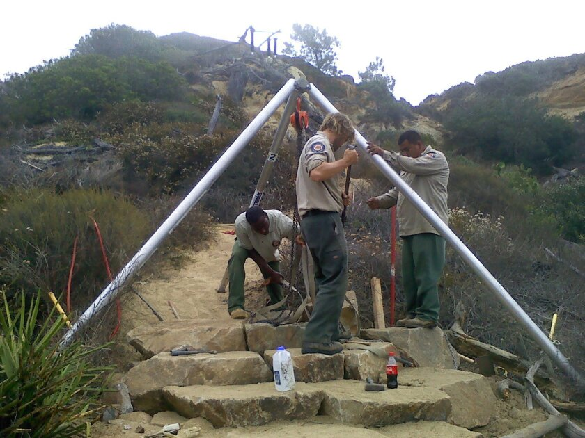 State workers put finishing touches on 113 new stone steps on Parry Grove Trail in Torrey Pines Reserve. The trail reopens officially Sunday, March 15.