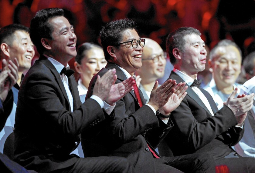 Wang Zhonglei, left, president of Huayi Bros. Media; Wang Zhongjun, chairman of Huayi Bros. Media; and director Feng Xiaogang attend the Huayi Bros. 20th anniversary ceremony China's Hainan province in 2014.