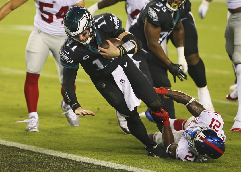 Philadelphia Eagles' Carson Wentz is tackled by New York Giants' Gabriel Peppers as he scores a rushing touchdown.