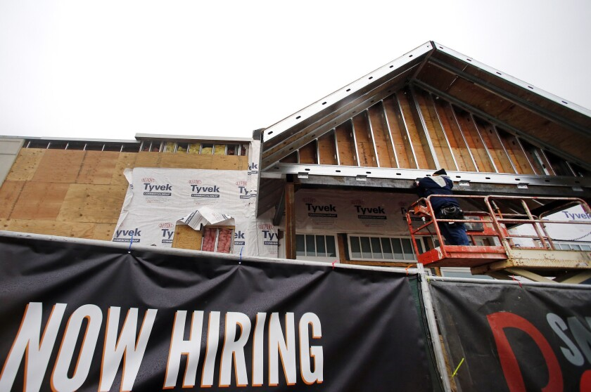"""A """"now hiring"""" sign hangs nearby as a builder works on a commercial property under construction in Peabody, Mass., on Jan. 12."""