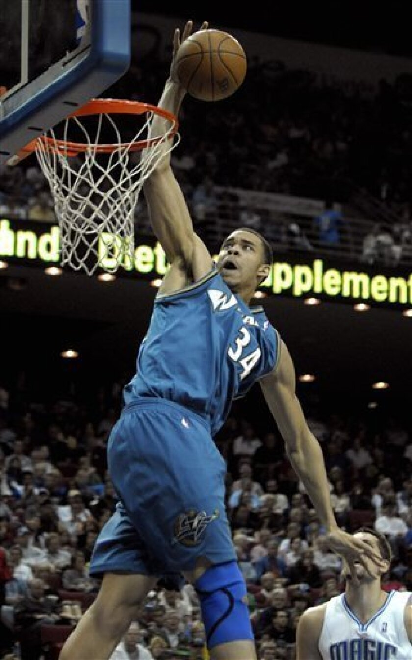 Washington Wizards center JaVale McGee, left, dunks the ball in front of Orlando Magic forward Ryan Anderson during the first half of an NBA basketball game in Orlando, Fla., Friday, Feb. 5, 2010. (AP Photo/Phelan M. Ebenhack)