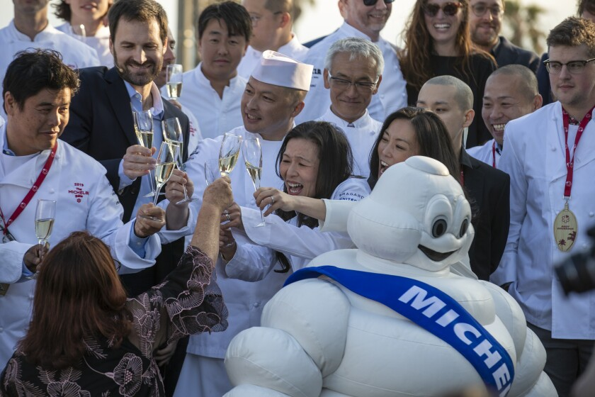 Two chefs raise their glasses in a toast while standing in front of a group of people and the white Michelin tire mascot.