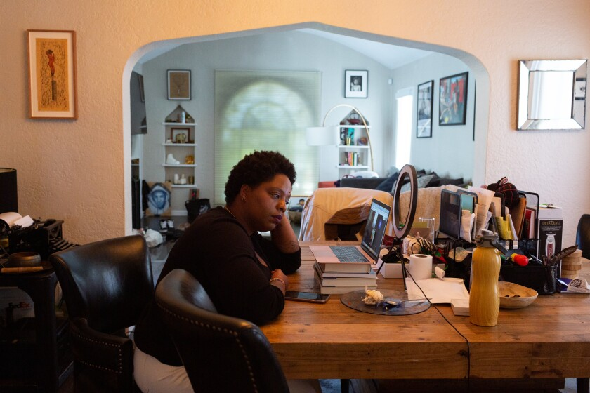 Patrisse Cullors takes a Zoom call at her dining room table.