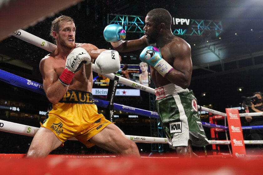 Floyd Mayweather, a la derecha,lanza un un puñetazo a Logan Paul, a la izquierda,