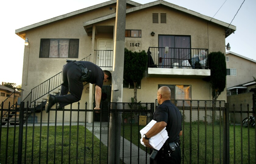 LAPD officers enter a housing complex in 2007 to serve notice of a gang injunction.