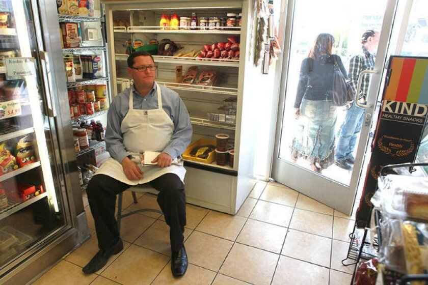 Rabbi Menachem Weiss, left, sits on a chair inside Doheny Glatt Kosher Meats.