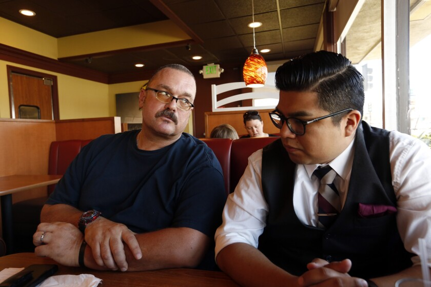 Rory Gallegos, left, talks with his housing advocate, Axel Cortes, about trying to find housing in Reseda.