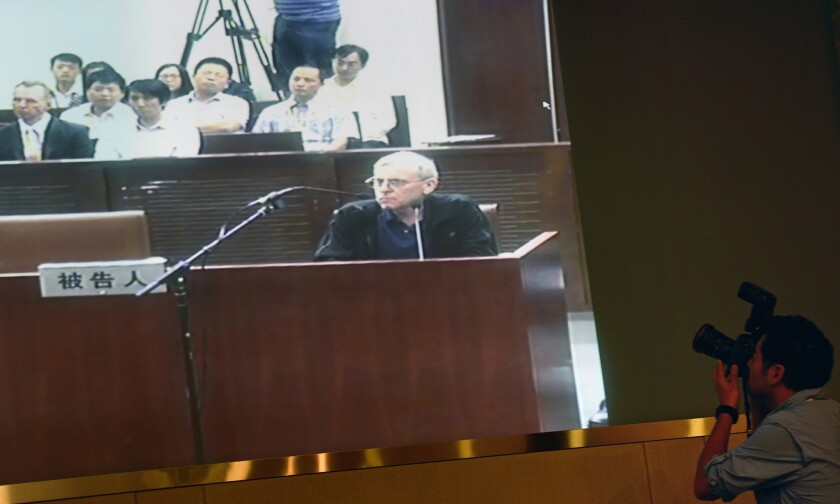 A TV screen shows the trial of British investigator Peter Humphrey and his wife at the Shanghai Intermediate Court on Aug. 8.
