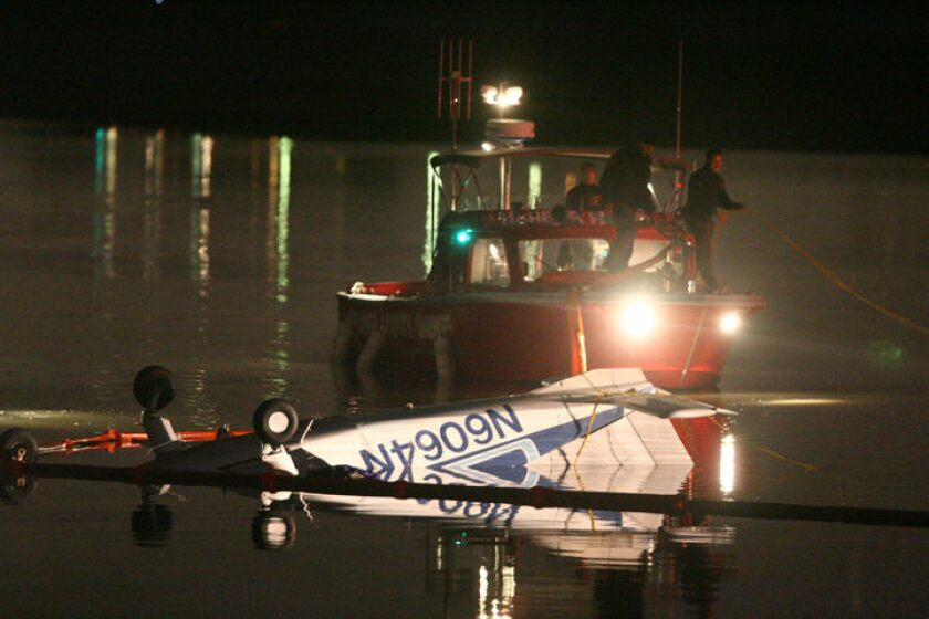 Orange County Sheriff personnel adjust a boom around a single-engine Beechcraft Muskateer airplane floating upside down in Upper Newport Bay on Sunday night. At least three people died in the crash, which occurred about 5:45 p.m.