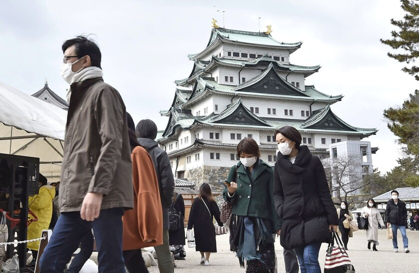 People wearing face masks visit Nagoya castle in Nagoya, central Japan, Sunday, Dec. 13, 2020. Japan's daily coronavirus cases have exceeded 3,000 for the first time while the government delays stricter measures for fear of hurting the economy ahead of the holiday season. (Kyodo News via AP)