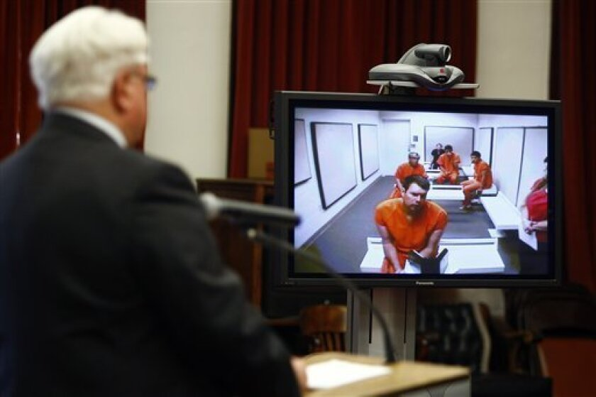 Former NFL quarterback Ryan Leaf makes an initial court appearance before Cascade County District Judge Dirk Sandefur via video link as his defense attorney, Eric Olson, listens at left, Monday, April 2, 2012, in Great Falls, Mont. Leaf was arrested again on Monday and is accused of committing anot