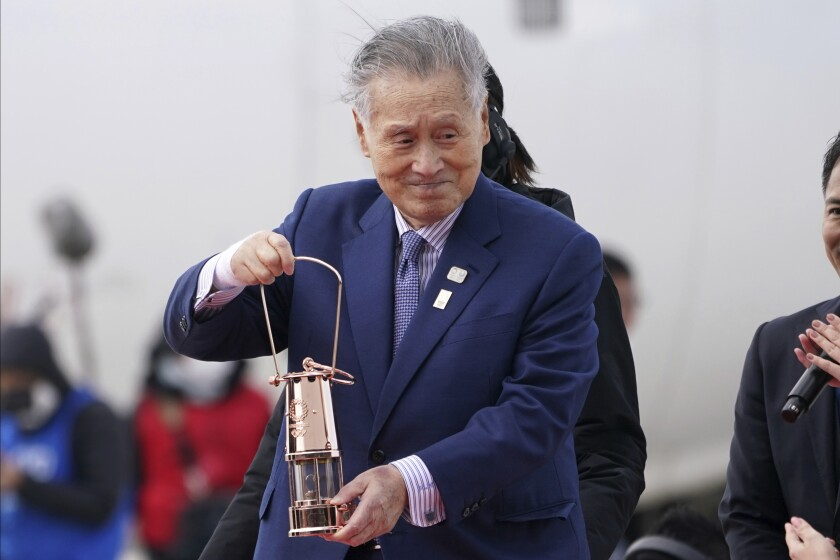 FILE - In this March 20, 2020, file photo, Tokyo 2020 Olympics chief Yoshiro Mori carries the Olympic flame during the Flame Arrival Ceremony at Japan Air Self-Defense Force Matsushima Base in Higashimatsushima in Miyagi Prefecture, north of Tokyo. Mori resigned Friday, Feb. 12, 2021 as the president of the Tokyo Olympic organizing committee following sexist comments implying women talk too much. (AP Photo/Eugene Hoshiko, File)