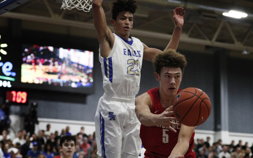 Mater Dei guard Devin Askew (5) passes after having his drive cut off by Santa Margarita's Max Agbonkpolo during a Trinity League game on Jan. 16.