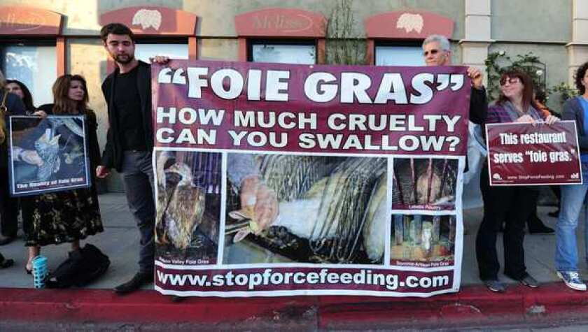 """Protesters hold a banner and placards while shouting slogans in front of the """"Melisse"""" eatery in Santa Monica, California, which sells foie gras dishes. A simmering row between animal rights campaigners and a handful of California's top chefs is coming to the boil, ahead of a looming ban on foie gras in California to take place July 1."""