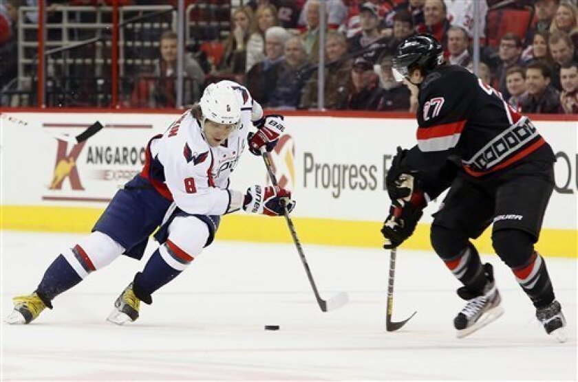 Washington Capitals' Alex Ovechkin (8), of Russia, controls the puck against Carolina Hurricanes' Justin Faulk (27) during the first period of an NHL hockey game on Thursday, March 14, 2013, in Raleigh, N.C. (AP Photo/Karl B DeBlaker)