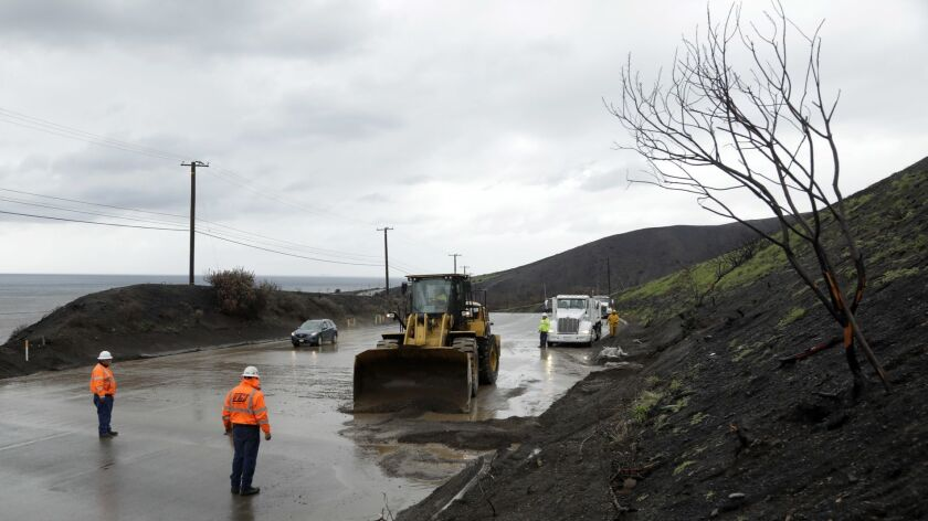 MALIBU, CA-JANUARY 14, 2019: A crew works to clear a small mudslide along the Pacific Coast Highway