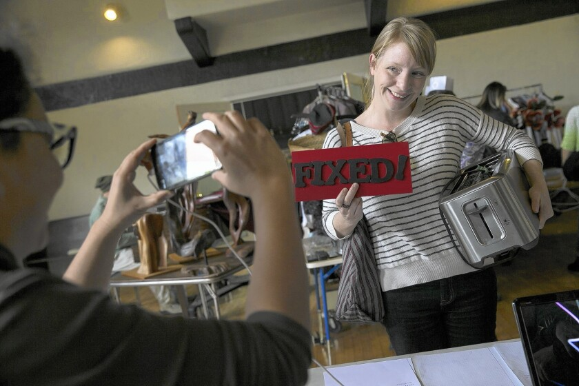 """A happy Jessica Ferree poses with a """"Fixed!"""" sign after her toaster was repaired by a volunteer at the monthly Repair Cafe event at a church hall in Pasadena."""