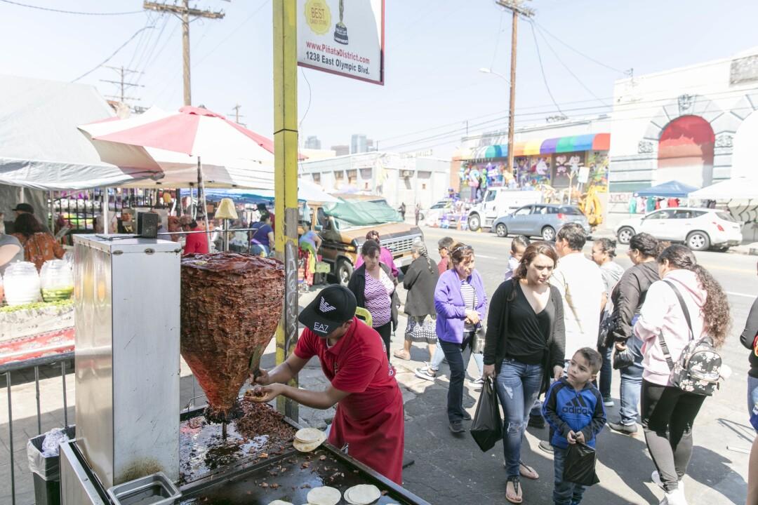 Tobias Martinez of Tacos el Chivo cuts meat for tacos al pastor at the Piñata District.