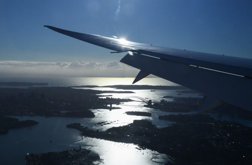 An aerial view of Sydney, including its famous bridge, and a wing as the plane approaches its landing.