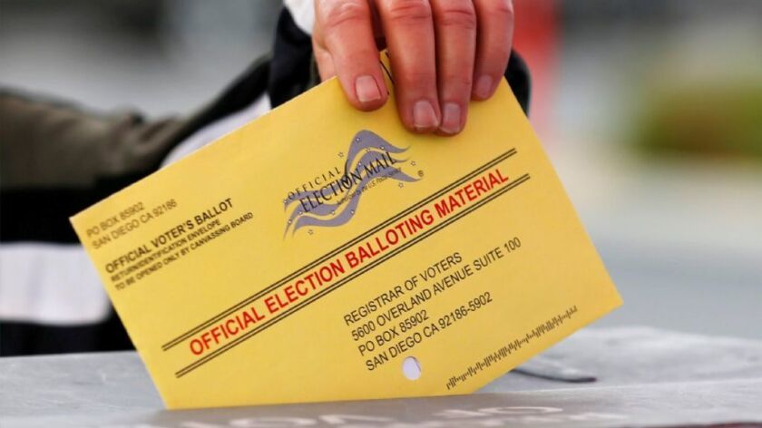 A poll worker places a mail-in ballot into a voting box as voters drop off their ballot in the U.S. presidential primary election in San Diego