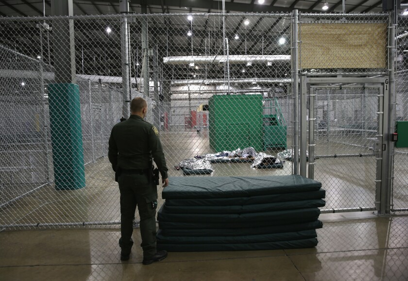 A U.S. Border Patrol agent watches as girls from Central America sleep under a thermal blanket at a detention facility run by the Border Patrol on September 8, 2014 in McAllen, Texas.