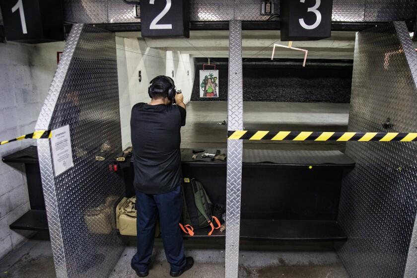 A man points a handgun downrange at a shooting range