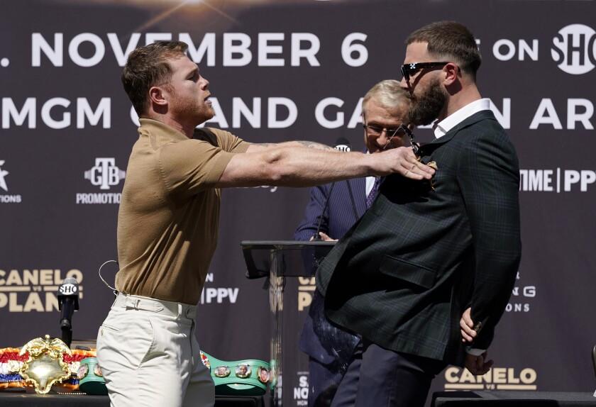 El boxeador mexicano Canelo Alvarez empuja al campeón de peso medio de la IBF Caleb Plant durante la conferencia de prensa previa a la pelea de noviembre del 6 de noviembre del 2021. (AP Photo/Mark J. Terrill)
