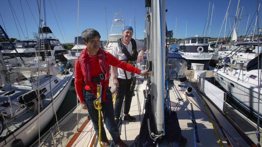 "Blind sailor Mitsuhiro ""Hiro"" Iwamoto, foreground and Doug Smith stand on the deck of Smith's 40-foot sailboat, Dream Weaver in San Diego harbor on Tuesday. The duo leaves Sunday, Feb. 24, on a planned wo-month, 6,000-mile nonstop sailing to Fukushima, Japan."