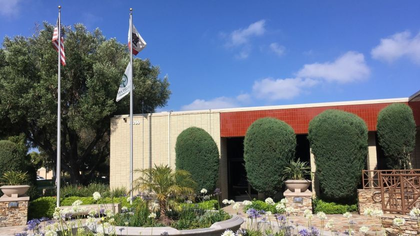Photo of municipal building blue sky and clouds in background and two flag poles in foreground flying U.S. and California flags and a Tree City USA flag.