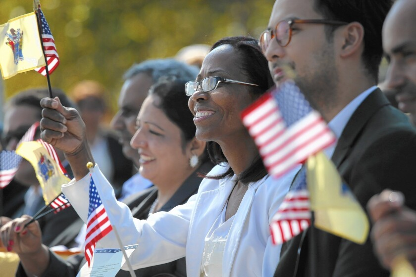 New American citizens wave flags after taking the oath of citizenship at Liberty State Park in Jersey City, N.J.