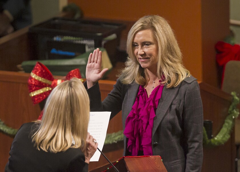 Huntington Beach Mayor Lyn Semeta, right, shown being sworn in as a City Council member in 2016, helped develop the city's COVID-19 Economic Recovery Task Force.