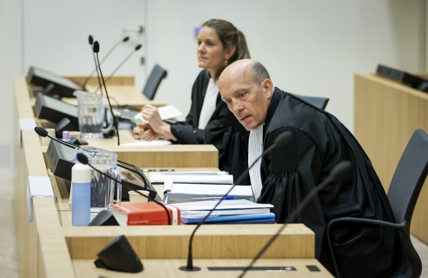 Sabine ten Doesschate, rear, and Boudewijn van Eijck, lawyers for one of the four suspects, Russian Oleg Pulatov, are seen as the trial resumed at the high security court building at Schiphol Airport, near Amsterdam, Monday, June 8, 2020, for three Russians and a Ukrainian charged with crimes including murder for their alleged roles in the shooting down of Malaysia Airlines Flight MH17 over eastern Ukraine nearly six years ago. (AP Photo/Robin van Lonkhuijsen, POOL)