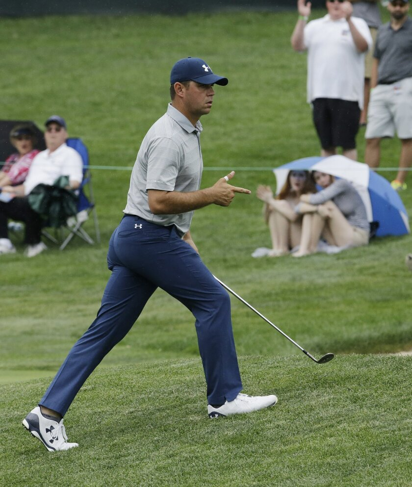 Gary Woodland reacts after chipping in on the 14th hole during the third round of the Memorial golf tournament, Saturday, June 4, 2016, in Dublin, Ohio. (AP Photo/Darron Cummings)