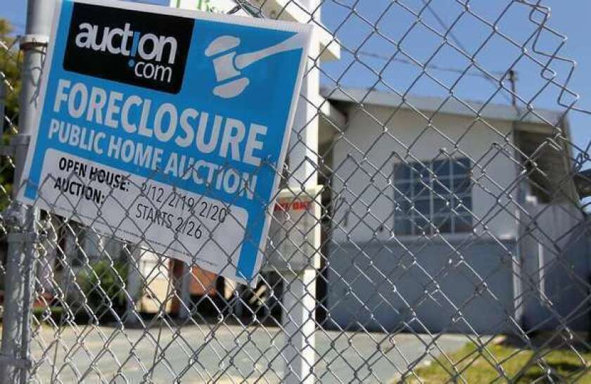 A foreclosure sign hangs on a fence in front of a home in Richmond in 2011. The city is adopting a plan that could use its eminent domain powers to seize underwater mortgages.