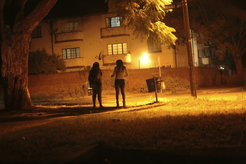 Sex workers wait for clients in the red light district of Harare, Zimbabwe, on June 12.