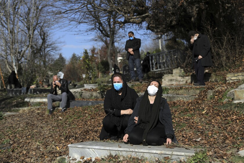 Mourners at a cemetery are socially distanced and masked at an outdoor funeral.