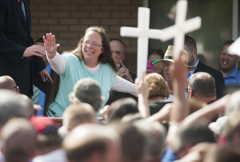 Kim Davis waves to supporters holding crosses in front of a Grayson, Ky., detention center on Sept. 8.