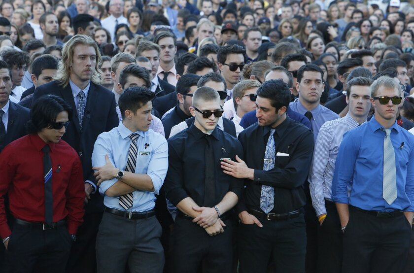 Nick Prato, center, one of the victims of the Oct. 9, 2015 shooting incident on the Northern Arizona University campus, stands with fellow fraternity members during a gathering four days later in Flagstaff, Ariz., to honor Colin Braugh, who was killed, and the three other student shooting victims.